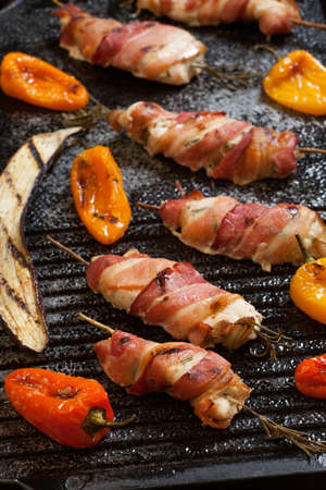 tenders: Grilled baconwrapped chicken tenders with lemon and rosemary on the grill wih grilled vegetables  peppers and and eggplant. Stock Photo