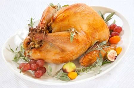 Roasted turkey on tray garnished with red grapes figs kumquat and herbs over white background