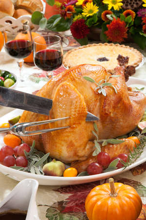 Carving roasted turkey on a server tray garnished with fresh figs grape kumquat and herbs on fall harvest table. Red wine side dishes pie and gravy. Decoraded with mini pumpkins candels and flowers. Stock Photo