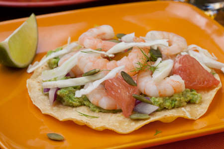 Two plates of shrimp ceviche tostadas with fennel and grapefruit beer garnished with mini bell pepper. Stock Photo