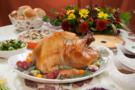 Roasted turkey on a server tray garnished with fresh figs grape kumquat and herbs on fall harvest table. Red wine side dishes pie and gravy. Decoraded with mini pumpkins candels and flowers.