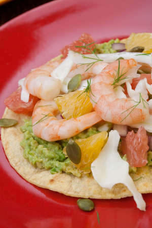 Two plates of shrimp ceviche tostadas with fennel and grapefruit, beer, garnished with mini bell pepper.