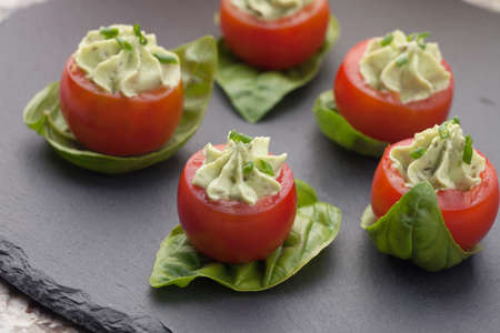 spread: Closeup of avocado cream cheese stuffed campari tomatoes on basil leaves. Couple of tropical cocktail drinks in background. Stock Photo