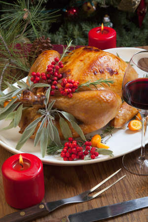 traditional christmas dinner: Roasted turkey garnished with sage, rosemary, and red berries in a tray prepared for Christmas dinner. Holiday table, candles and Christmas tree with ornaments. Stock Photo