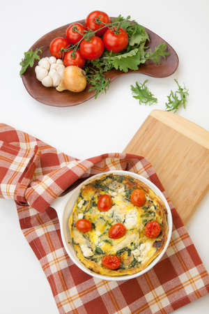 sundried: Closeup of pan with fresh made frittata with baby kale, sundried tomatoes, and goat cheese.