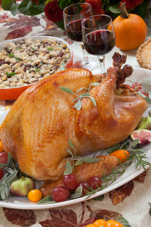 side dishes: Roasted turkey on a server tray garnished with fresh figs, grape, kumquat, and herbs on fall harvest table. Red wine, side dishes, pie, and gravy. Decoraded with mini pumpkins, candels, and flowers.