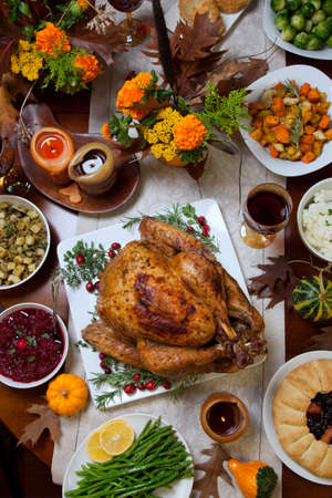 turkey: Pavo asado con guarnici�n de ar�ndanos sobre una mesa r�stica decoraded con calabazas, calabazas, esp�rragos, coles de Bruselas, verduras al horno, pastel, flores y velas.