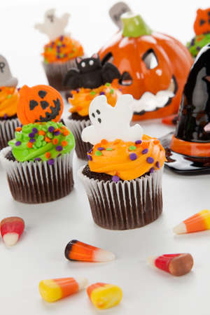 Halloween cupcake with ghost decorations surrounded by Halloween cupcakes, corn candies, and decoration. Stock Photo
