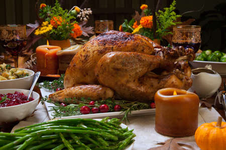 thanksgiving: Roasted turkey garnished with cranberries on a rustic style table decoraded with pumpkins, gourds, asparagus, brussel sprouts, baked vegetables, pie, flowers, and candles. Stock Photo