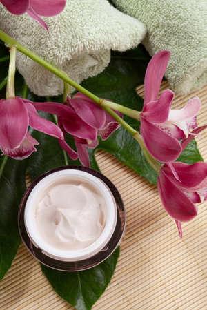 cremas faciales: Rosa oscuro florecen las flores de orqu�deas Cymbidium y crema facial hidratante para todos los d�as. Foto de archivo