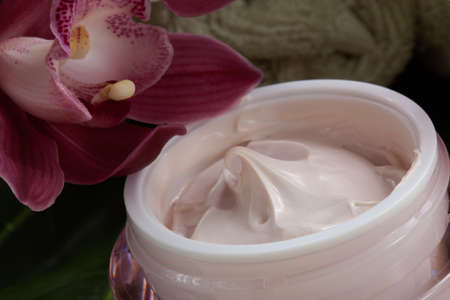 natural beauty: Dark pink blooming Cymbidium orchid flowers and moisturizing face cream for everyday.