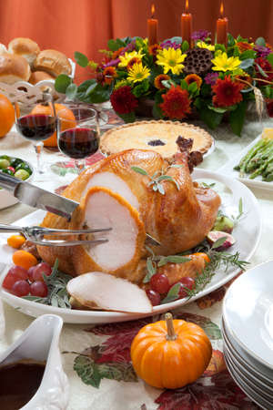 side dishes: Carving roasted turkey on a server tray garnished with fresh figs, grape, kumquat, and herbs on fall harvest table. Red wine, side dishes, pie, and gravy. Decoraded with mini pumpkins, candels, and flowers.