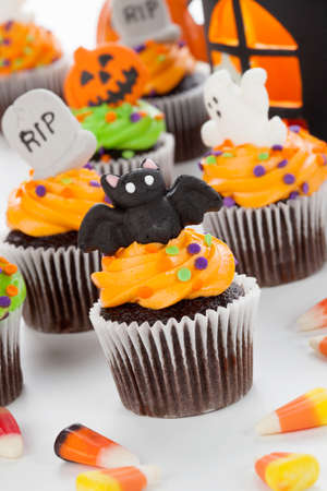 cupcakes: Halloween cupcake with bat, ghost, and RIP decorations surrounded by Halloween cupcakes, corn candies, and decoration.