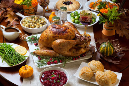 Roasted turkey garnished with cranberries on a rustic style table decoraded with pumpkins, gourds, asparagus, brussel sprouts, baked vegetables, pie, flowers, and candles. Archivio Fotografico