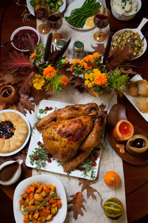 thanksgiving dinner: Roasted turkey garnished with cranberries on a rustic style table decoraded with pumpkins, gourds, asparagus, brussel sprouts, baked vegetables, pie, flowers, and candles. Stock Photo