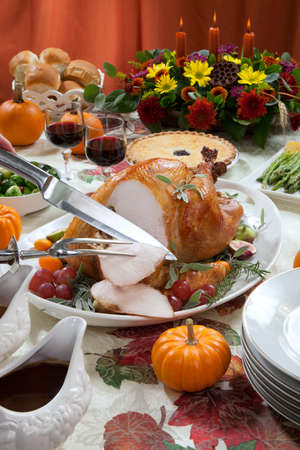 fall harvest: Carving roasted turkey on a server tray garnished with fresh figs, grape, kumquat, and herbs on fall harvest table. Red wine, side dishes, pie, and gravy. Decoraded with mini pumpkins, candels, and flowers.