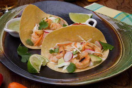 shrimp: Two shrimp tacos with salsa, guacamole, beer, garnished with mini bell pepper and lime.