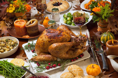 feasts: Roasted turkey garnished with cranberries on a rustic style table decoraded with pumpkins, gourds, asparagus, brussel sprouts, baked vegetables, pie, flowers, and candles. Stock Photo