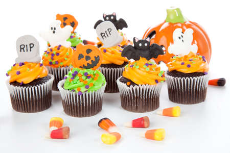 Halloween cupcake with RIP, ghost, bat, and  jack-o-lantern decorations surrounded by Halloween cupcakes, corn candies, and decoration. Stock Photo