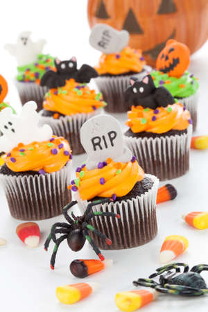 cupcakes: Halloween cupcake with RIP, ghost, and bat decorations surrounded by Halloween cupcakes, corn candies, and decoration.