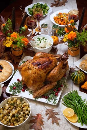 Roasted turkey garnished with cranberries on a rustic style table decoraded with pumpkins, gourds, asparagus, brussel sprouts, baked vegetables, pie, flowers, and candles. Imagens