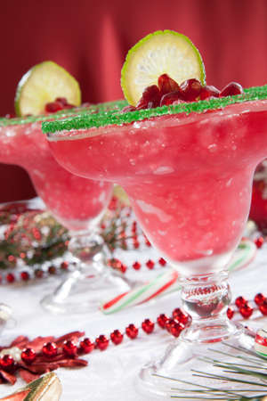 margaritas: Two frozen pomegranate margaritas cocktails on Christmas decorated holiday table with Christmas ornaments. Holiday cocktails series.