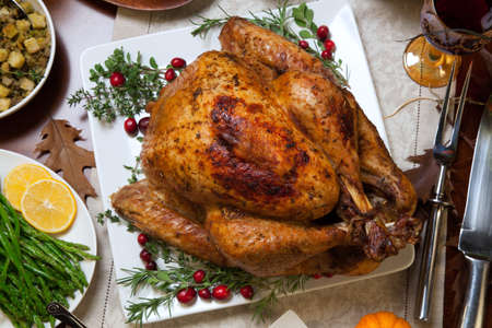 pavo: Roasted turkey garnished with cranberries on a rustic style table decoraded with pumpkins, gourds, asparagus, brussel sprouts, baked vegetables, pie, flowers, and candles. Foto de archivo