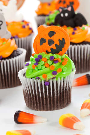 cupcakes: Halloween cupcake with jack-o-lantern and bat decorations surrounded by Halloween cupcakes, corn candies, and decoration.
