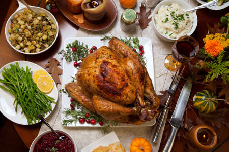 Roasted turkey garnished with cranberries on a rustic style table decoraded with pumpkins, gourds, asparagus, brussel sprouts, baked vegetables, pie, flowers, and candles. Stock Photo