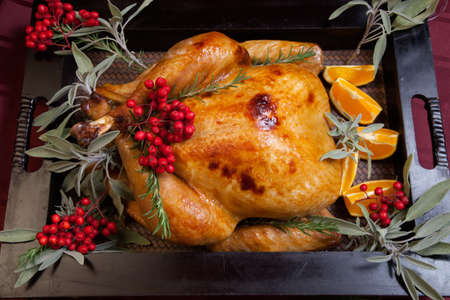 dinner: Roasted turkey garnished with sage, rosemary, and red berries in a tray prepared for Christmas dinner. Holiday table, candles and Christmas tree with ornaments. Stock Photo