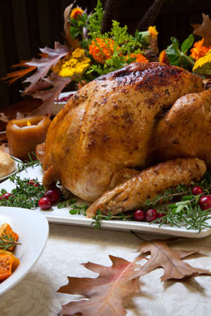 stuffing: Roasted turkey garnished with cranberries on a rustic style table decoraded with pumpkins, gourds, asparagus, brussel sprouts, baked vegetables, pie, flowers, and candles. Stock Photo