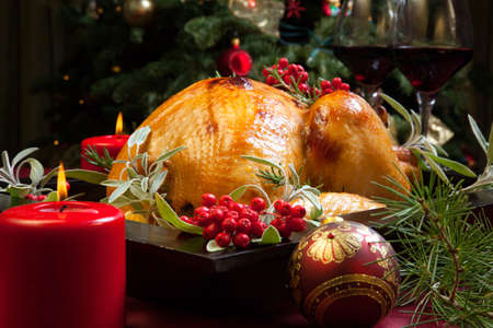 feast: Roasted turkey garnished with sage, rosemary, and red berries in a tray prepared for Christmas dinner. Holiday table, candles and Christmas tree with ornaments. Stock Photo