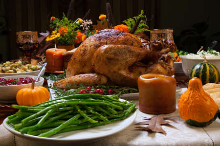 table: Roasted turkey garnished with cranberries on a rustic style table decoraded with pumpkins, gourds, asparagus, brussel sprouts, baked vegetables, pie, flowers, and candles. Stock Photo