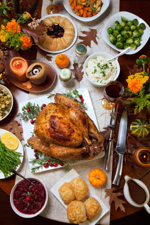 Roasted turkey garnished with cranberries on a rustic style table decoraded with pumpkins, gourds, asparagus, brussel sprouts, baked vegetables, pie, flowers, and candles. Zdjęcie Seryjne