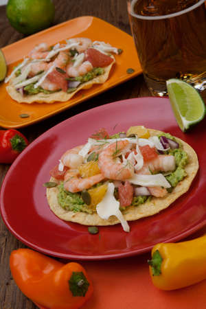 fennel seed: Two plates of shrimp ceviche tostadas with fennel and grapefruit, beer, garnished with mini bell pepper.