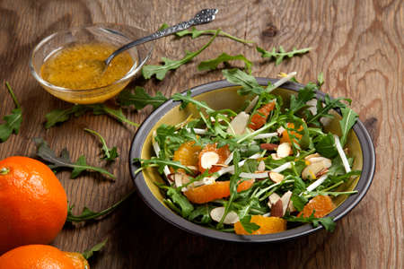 Closeup of a plate of arugula salad with mandarins, oranges, beans sprouts, and sliced almonds served with mandarin vinaigrette for healthy lunch. Imagens