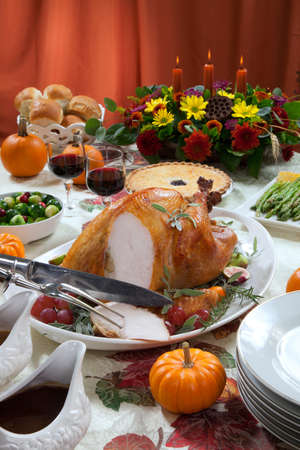 carvings: Carving roasted turkey on a server tray garnished with fresh figs, grape, kumquat, and herbs on fall harvest table. Red wine, side dishes, pie, and gravy. Decoraded with mini pumpkins, candels, and flowers.