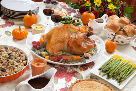 thanksgiving food: Roasted turkey on a server tray garnished with fresh figs, grape, kumquat, and herbs on fall harvest table. Red wine, side dishes, pie, and gravy. Decoraded with mini pumpkins, candels, and flowers.
