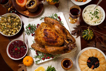 garnished: Roasted turkey garnished with cranberries on a rustic style table decoraded with pumpkins, gourds, asparagus, brussel sprouts, baked vegetables, pie, flowers, and candles. Stock Photo
