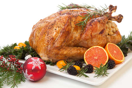 garnished: Roasted stuffed turkey garnished with fresh fruits and herbs for holiday dinner.