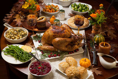 meal: Roasted turkey garnished with cranberries on a rustic style table decoraded with pumpkins, gourds, asparagus, brussel sprouts, baked vegetables, pie, flowers, and candles. Stock Photo