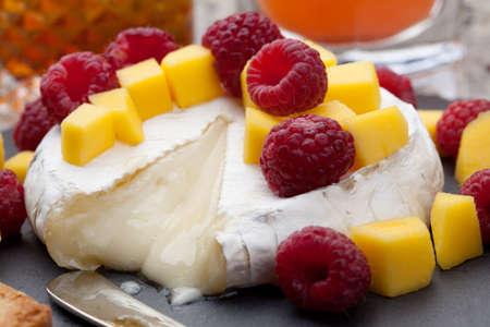 queso: Queso caliente al horno brie con mango fresco y frambuesas - gran merienda para c�ctel. Un par de c�cteles en el fondo. Foto de archivo