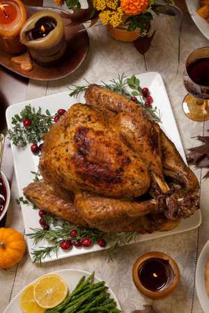 turquia: Pavo asado con guarnici�n de ar�ndanos sobre una mesa r�stica decoraded con calabazas, calabazas, esp�rragos, coles de Bruselas, verduras al horno, pastel, flores y velas.