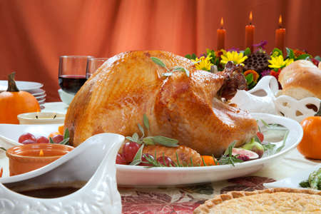 server side: Roasted turkey on a server tray garnished with fresh figs, grape, kumquat, and herbs on fall harvest table. Red wine, side dishes, pie, and gravy. Decoraded with mini pumpkins, candels, and flowers.