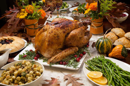 Roasted turkey garnished with cranberries on a rustic style table decoraded with pumpkins, gourds, asparagus, brussel sprouts, baked vegetables, pie, flowers, and candles. Reklamní fotografie - 48345610