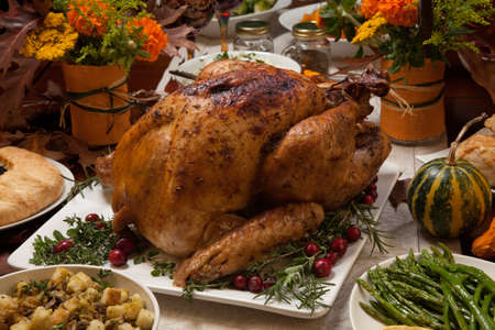 thanksgiving feast: Roasted turkey garnished with cranberries on a rustic style table decoraded with pumpkins, gourds, asparagus, brussel sprouts, baked vegetables, pie, flowers, and candles. Stock Photo