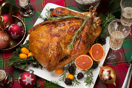 dinner food: Roasted turkey with fresh fruits, flutes of champagne, Christmas tree, candles, and decorations