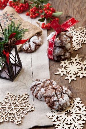 chocolate cookies: Closeup of melty Chocolate - Truffle cookies on holiday table. Christmas ornaments, decorations, and red berries.
