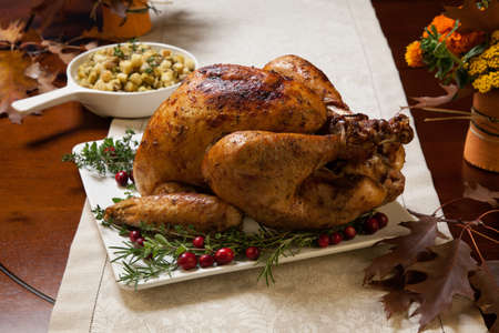 roasted turkey: Roasted turkey garnished with cranberries on a rustic style table decoraded with pumpkins, gourds, asparagus, brussel sprouts, baked vegetables, pie, flowers, and candles. Stock Photo