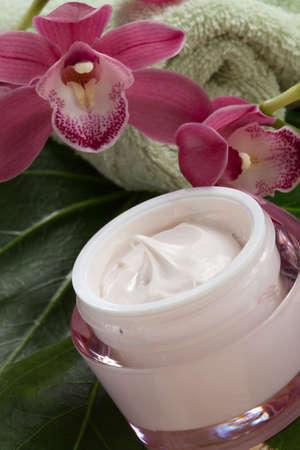 cremas faciales: Rosa oscuro florecen las flores de orquídeas Cymbidium y crema facial hidratante para todos los días. Foto de archivo